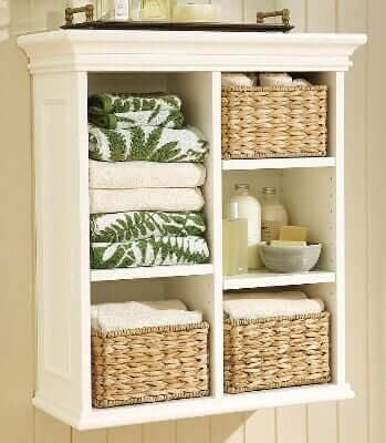 Stick the basket on the wall upside down and make room to store the towels